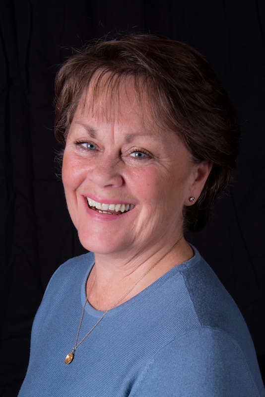 headshot of Dee Hartmann in blue gray top