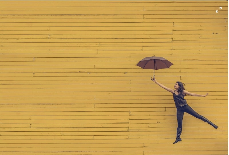 Woman with umbrella jumping in front of yellow building